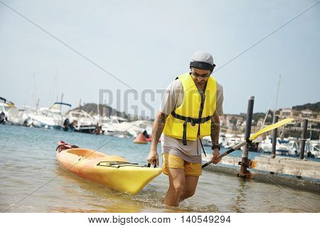 Back Shot Of A Sportsman With Tattoos Pulling Kayak Or Canoe Out Of The Sea, Standing Against Blurre