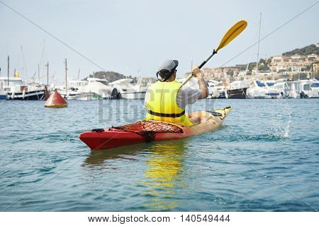 Young Man Paddling On Red Kayak On The Sea Near Ships And Yachts. Tourist Making Splashes With Paddl