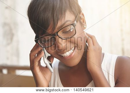 Smiling Brown-skinned Girl Talking On Phone. Lovely Spanish Woman With Stylish Short Haircut And Shi