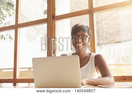 Smiling Dark-skinned Girl Sitting And Working On Light Veranda Near The Window. Young Female Entrepr