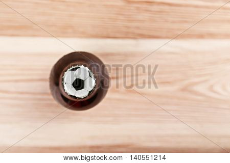 Bottle of beer with football ball symbol on cap, on wooden table, top view
