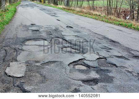 Dangerous road with holes destroyed asphalt way