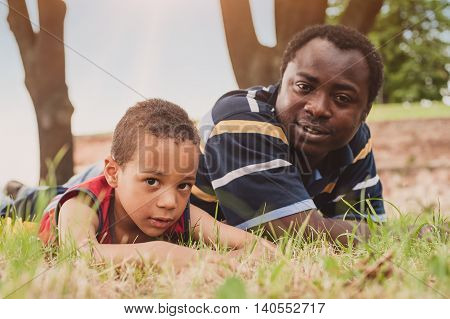 Father and son having fun and lying on the grass and enjoying in park