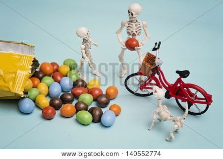 Skeleton and his skeleton kid and their dog getting chocolate candy with bicycle