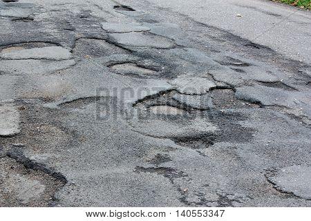 Dangerous asphalt road with holes destroyed asphalt