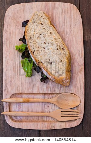 Close up of fresh organic sandwich bread fill with fresh vegetable on wooden dish.