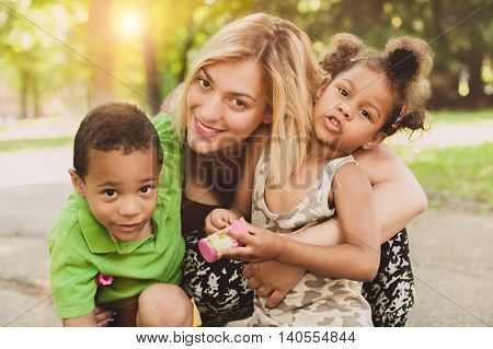 Mother son and daughter having fun and enjoying in the park. International family