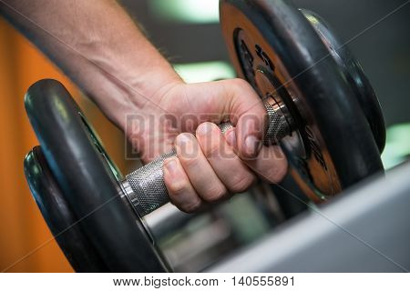 Close-up image of male hand holding dumbbell