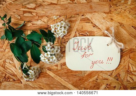 Small Yellow Wish Card with White Flowers and Green Leaves on the Texture Wooden Background.Top View
