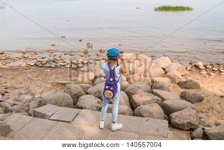 Little girl stands on the shore and seascape photographs