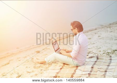 Toned picture of middle-aged poet working on his laptop computer. Handsome businessman in glasses making diagrams for new projects in evening near by sea.
