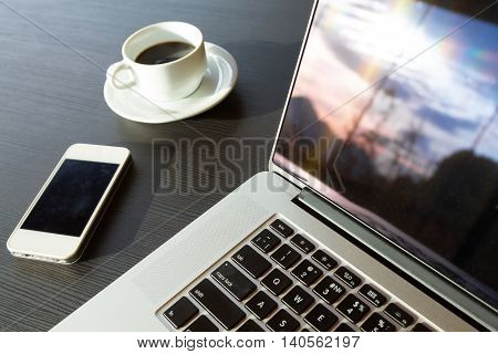 Laptop Telephone and Coffee on black wood Table Nature Mountain and Sunrise view reflection in Computer Screen