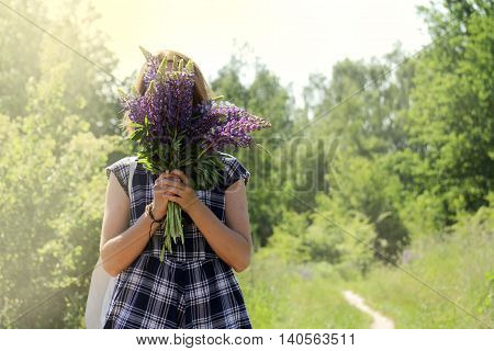 girl in a plaid summer dress hiding her face behind a bouquet of wild flowers / floral hide and seek outdoors
