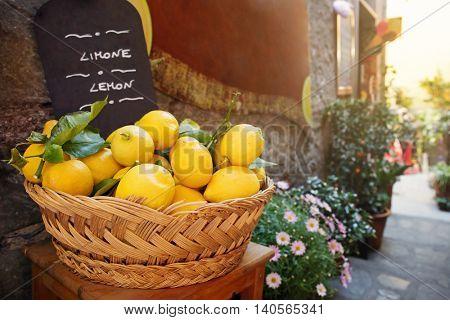 Wicker basket full of lemons on the italian street od Corniglia