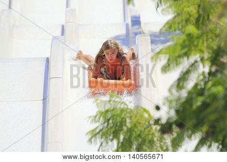 Rhodes Greece-July 25 2016:Young happy girl on the mat racer slide.Mat racer slide is very popular for young people in the Water Park.Water Water Park is located in Faliraki on the island of Rhodes in Greece and one of the most largest in Europe and