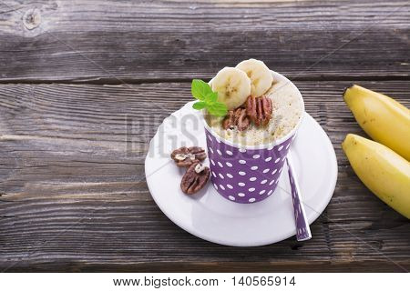 Quick breakfast in the microwave for five minutes. Homemade banana cup cakes in paper cups for portioned snack. two portions with pecan and banana slices, fresh mint