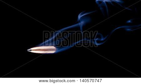 Copper plated bullet with a polymer tip and smoke trailing behind