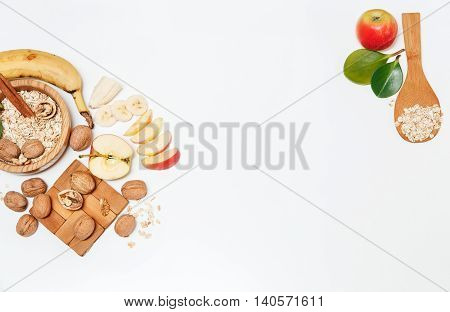 There are Banana, Apple, Orange with Walnuts in the Wooden Plate and Rolled Oats, Wooden Spoon, Trivet, with Green Leaves, Healthy Fresh Organic Food on the White Background, Top View
