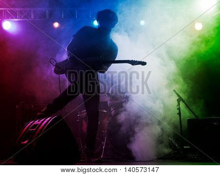 Silhouette of guitar player on stage. Dark background smoke spotlights