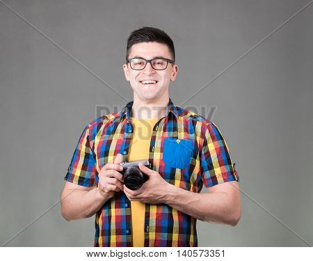 Handsome man dressed in a multicolored shirt with photo camera standing isolated on gray background