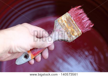 Painter is working on paint brush barrels of water with red paint / painting of work is finished