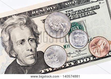 Twenty american dollars banknote, partial front face with coins of all denominations