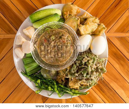 Fermented fish spicy dip with boiled eggs and vegetables in white dish .