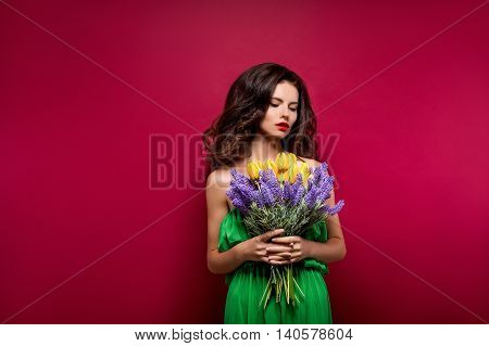 Long-haired seductive brunette with bouquet of flowers. Vinous background. Isolated
