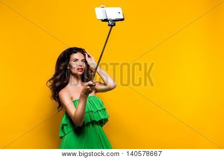 Portrait of young model in green dress and sunglasses posing while making selfie against yellow background.