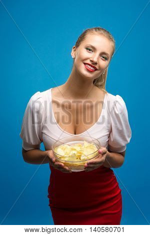 Portrait of fashionable young blond woman in pink-red dress, bright make-up holding, eating fried potato, chips and  over blue background. Unhealthy eating. Junk food concept.