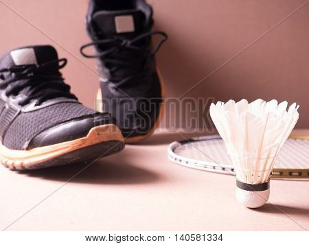 sports set of black orange sport shoes and shuttle cocks symbolic of man with badminton racket on sport background in concept family activity