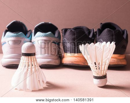 sports set of black orange sport shoes and blue sport shoe and shuttlecocks issymbolic of man and women on sport background in concept family activity