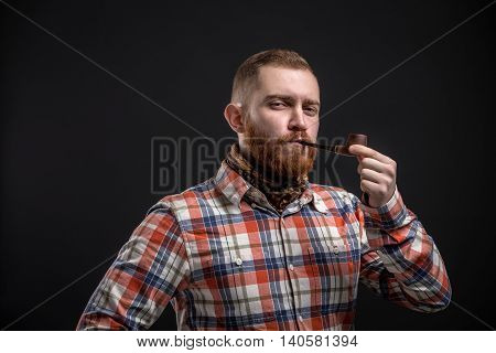 Portrait of handsome bearded man in checked shirt smoking pipe. Studio shot. Isolated