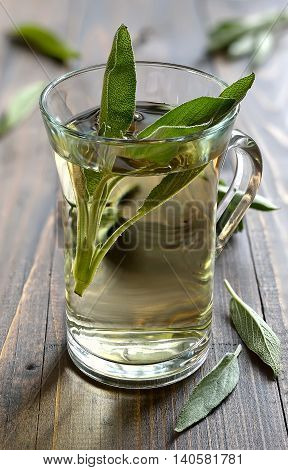 Glass of herbal sage tea made from freshly picked green sage leaves standing on a wooden surface