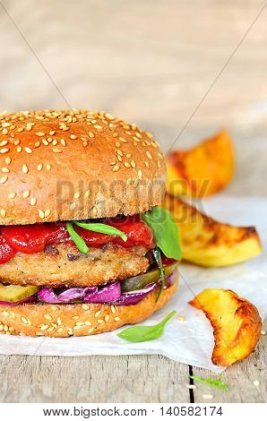 Crusty homemade burger with fresh salad leaves and fried potatoes