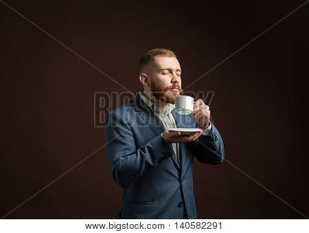 Portrait of elegant man in suit enjoying coffee smell with eyes closed.Isolated.