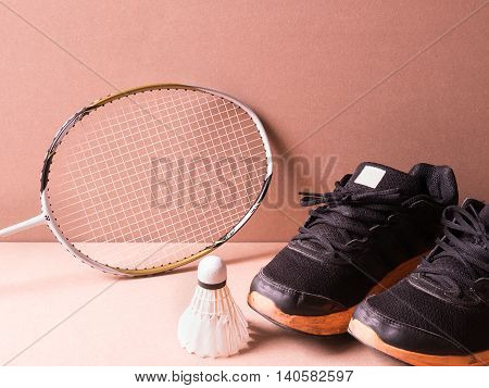sports set of black orange sport shoes and shuttlecocks with badminton racket on sport background