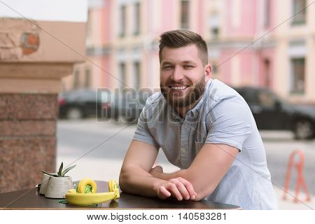 Picture of happy smiling handsome man sitting in outdoor vegan cafe and looking at camera. Bearded man waiting for his order or friends.