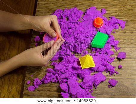 The female hands with pink kinetic sand