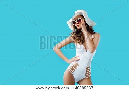 Attractive girl in a white bikini, hat, sunglasses, emotionally opened mouth on a bright blue background with a perfect body. Isolated. Studio shot.