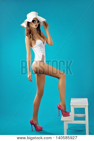 Portrait of attractive and sexy brunette model posing in white monokini and pink heels against of bright blue background. Isolated. Studio shot.