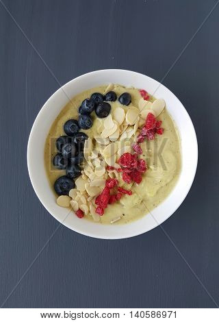 smoothie bowl with blueberry,raspberry and almond on a grey background