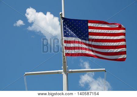 American flag flying from sailing mast with blue sky and puffy white clouds