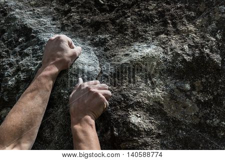 Two rough hands with taped fingers gripping a rock ledge during a bouldering.