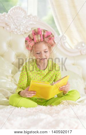 Happy cute little girl in hair curlers with book