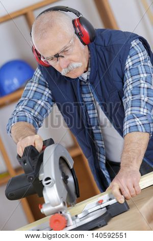 carpenter working in his workshop with circular saw