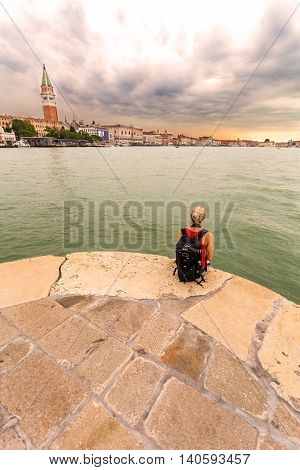 Female traveler sitting on a background of Venice landmark, view from the sea of Piazza San Marco or st Mark square, Campanile and PalazzoDucale or Doge Palace. Italy, Europe.