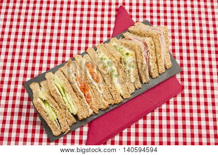 Sandwiches with various fillings A slate plate of different triangular sandwiches