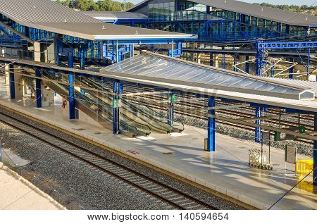 Modern railway station Camp de Tarragona (Spain): platforms tracks escalators. Horizontal.