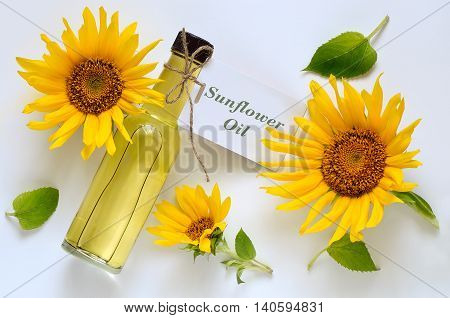 Sunflower oil in a glass bottle decorated with fresh sunflowers on a light background top view